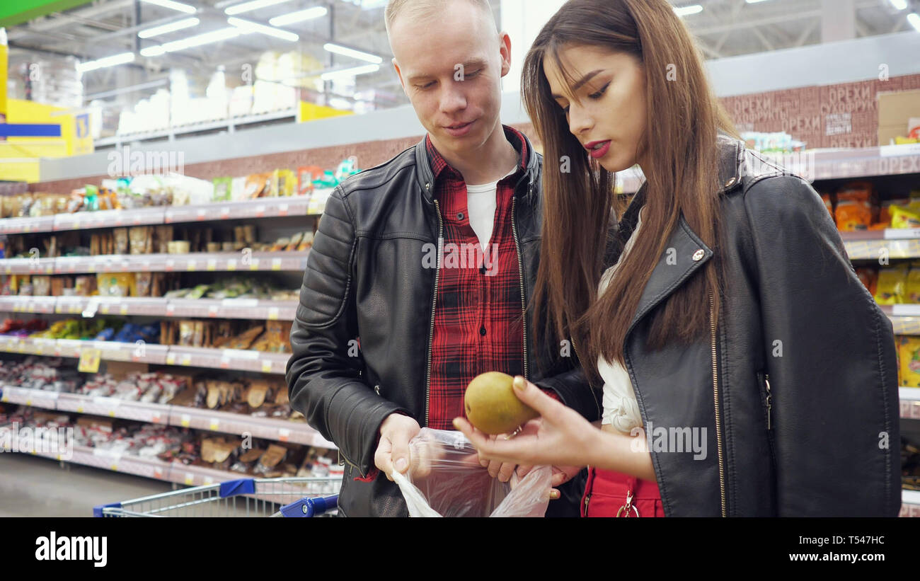 Young couple guy and girl buys pears in a supermarket, girl puts pears in plastic bag. Stock Photo