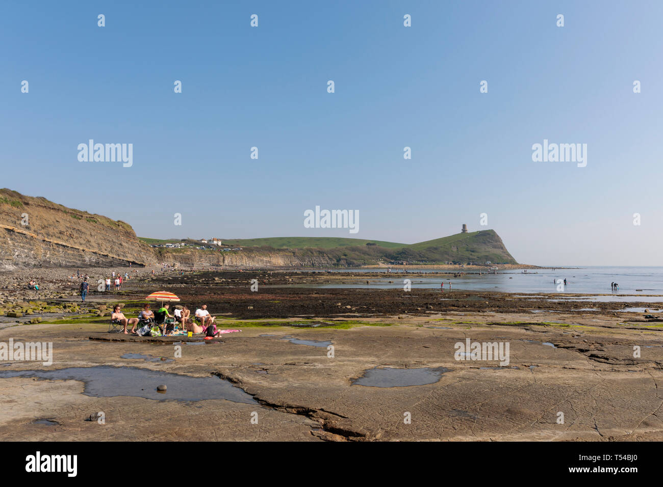 People enjoying the warm Easter Bank Holiday weather on the rock ledges at Kimmeridge Bay in Dorset 2019 - Stock Image