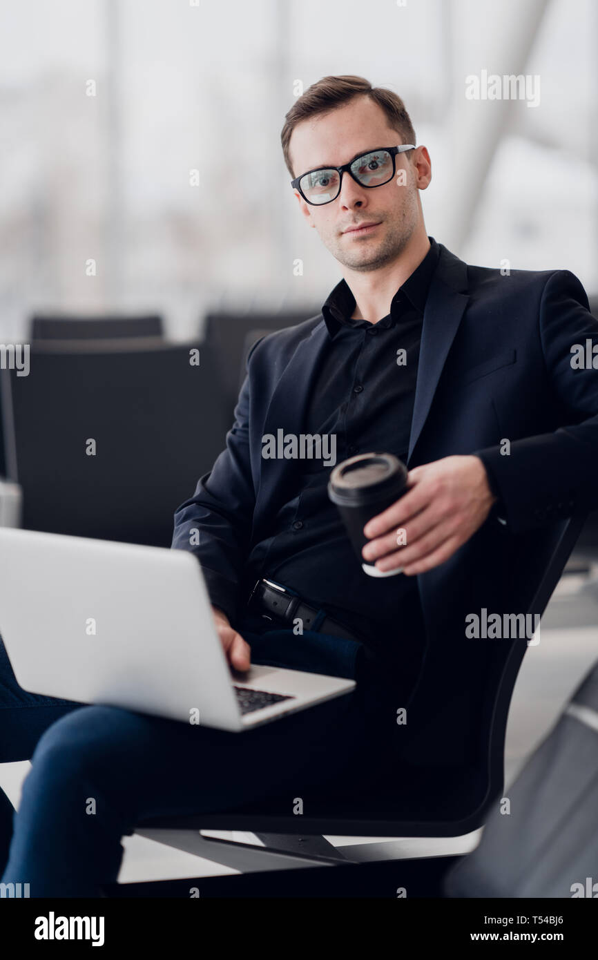 Handsome businessman writing massages with cup of coffee in airport - Stock Image