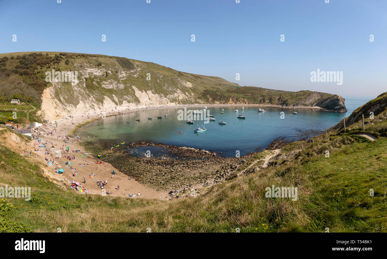 People enjoying the warm Easter Bank Holiday weather at Lulworth Cove in Dorset 2019 - Stock Image