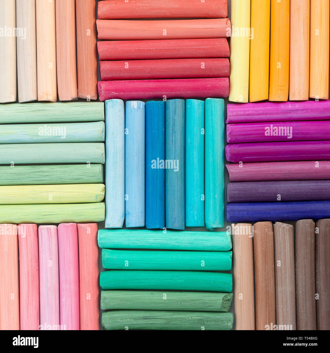 Rainbow pastel crayons in rows as background. Square image - Stock Image