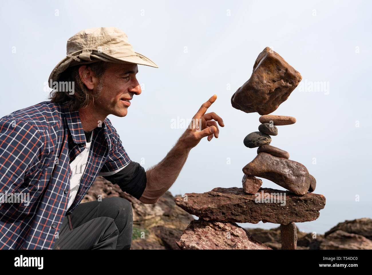 Dunbar, Scotland, UK. 20th Apr, 2019. Pedro Duran examines his sculpture on Eye Cave beach in Dunbar during opening day of the European Stone Stacking Championship 2019. Credit: Iain Masterton/Alamy Live News - Stock Image