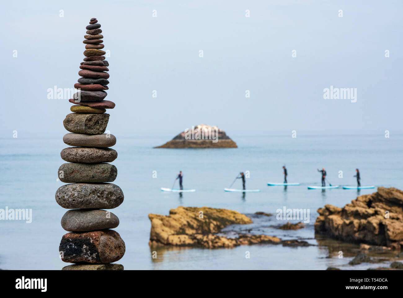 Dunbar, Scotland, UK. 20th Apr, 2019. Paddle boarders and stone stack at Eye Cave beach in Dunbar during opening day of the European Stone Stacking Championship 2019. Credit: Iain Masterton/Alamy Live News - Stock Image
