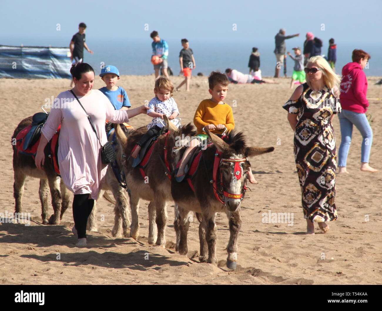 Skegness, UK. 20th Apr, 2019. Children seen riding the donkeys on the beach led in groups at walking pace during Easter. People enjoy the unseasonably warm Easter weather in the UK - especially the children having donkey rides on the sandy beach at Skegness. The traditional seaside attraction started in Victorian times, but is now seen much less in the major resorts, but is still popular on the Lincolnshire beaches of Skegness, Mablethorpe and Ingoldmells. Credit: SOPA Images Limited/Alamy Live News Stock Photo