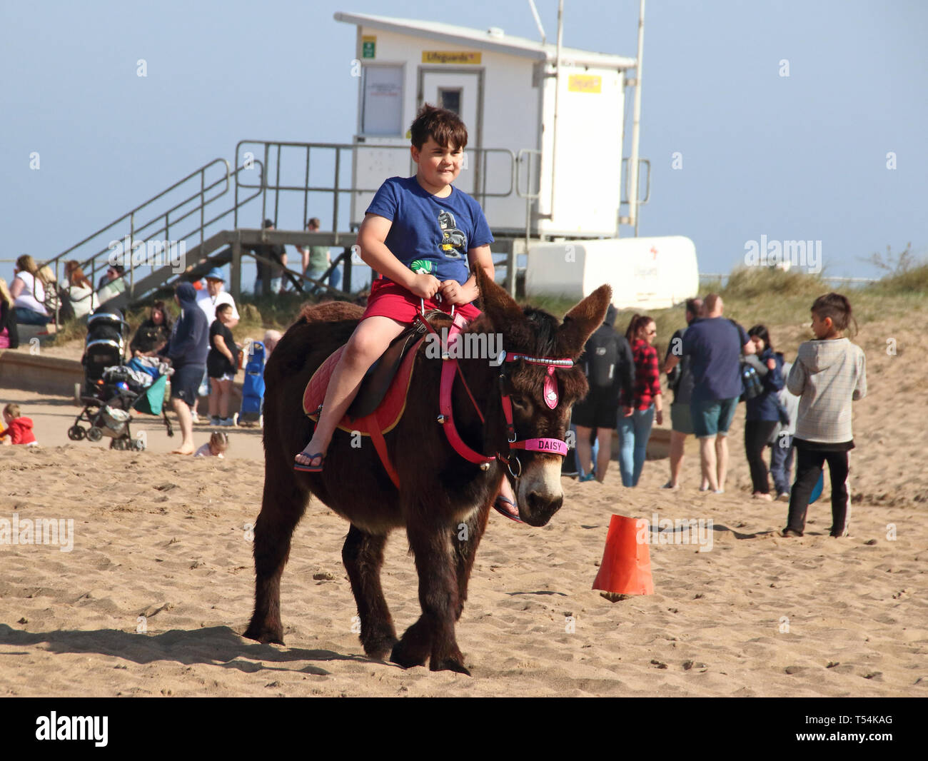 Skegness, UK. 20th Apr, 2019. Child seen riding a donkey on the beach at Skegness during Easter. People enjoy the unseasonably warm Easter weather in the UK - especially the children having donkey rides on the sandy beach at Skegness. The traditional seaside attraction started in Victorian times, but is now seen much less in the major resorts, but is still popular on the Lincolnshire beaches of Skegness, Mablethorpe and Ingoldmells. Credit: SOPA Images Limited/Alamy Live News Stock Photo