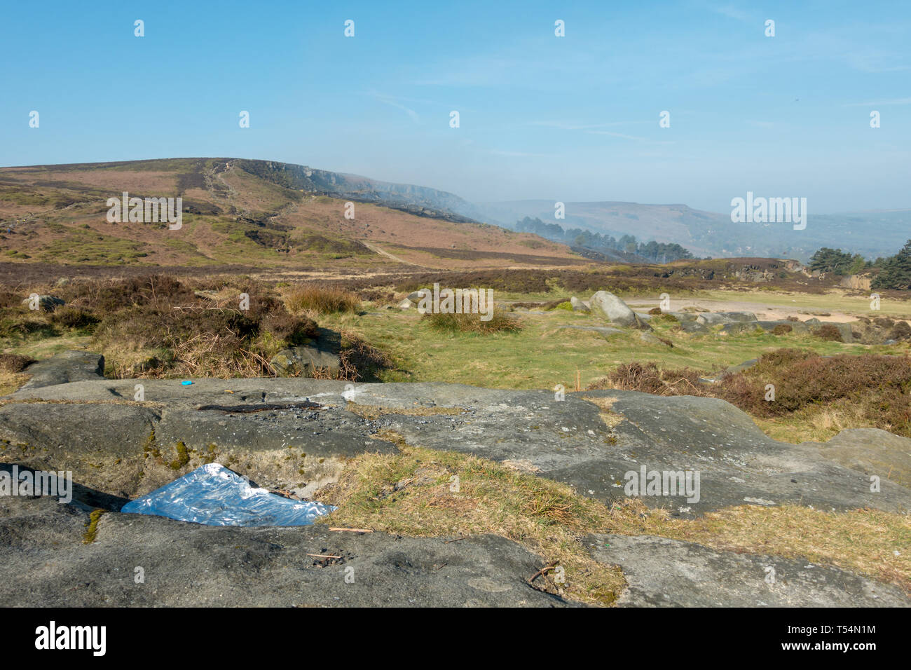 Yorkshire, UK. 21st April 2019.  Fire services continue efforts to extinguish fire on Ilkley Moor.  Discarded barbecue after yesterday's hot day with a burning moor in the background and locals and fire investigation officers question, 'what started it?' and the BBC reports arrests have been made. Credit: Rebecca Cole/Alamy Live News - Stock Image