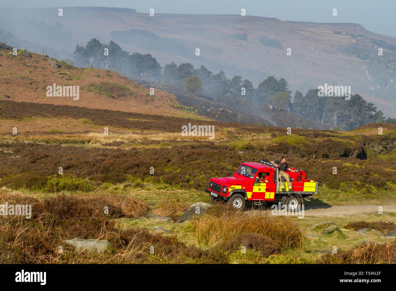UK Moorland Fire: Ilkley Moor, West Yorkshire, UK. 21st April 2019.  Firefighter sits on the back of a 4x4 fire truck as efforts continue to extinguish wildfire - the moors the morning after still clearly smoking.  Rebecca Cole/Alamy Live News - Stock Image