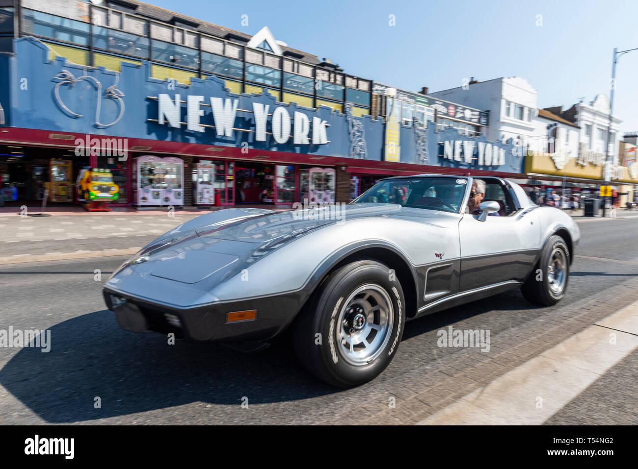 Classic car show taking place along the seafront at Marine Parade, Southend on Sea, Essex, UK. Chevrolet Corvette Stingray driving past New York amusement arcade Stock Photo