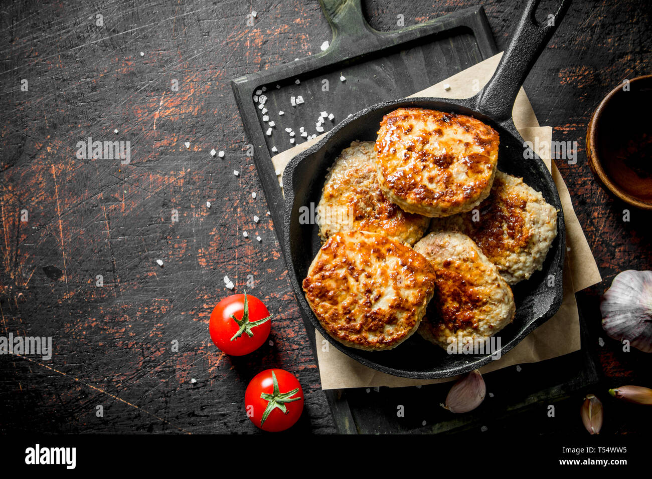 Cutlets in the pan on the paper with garlic and tomatoes. On dark rustic background Stock Photo