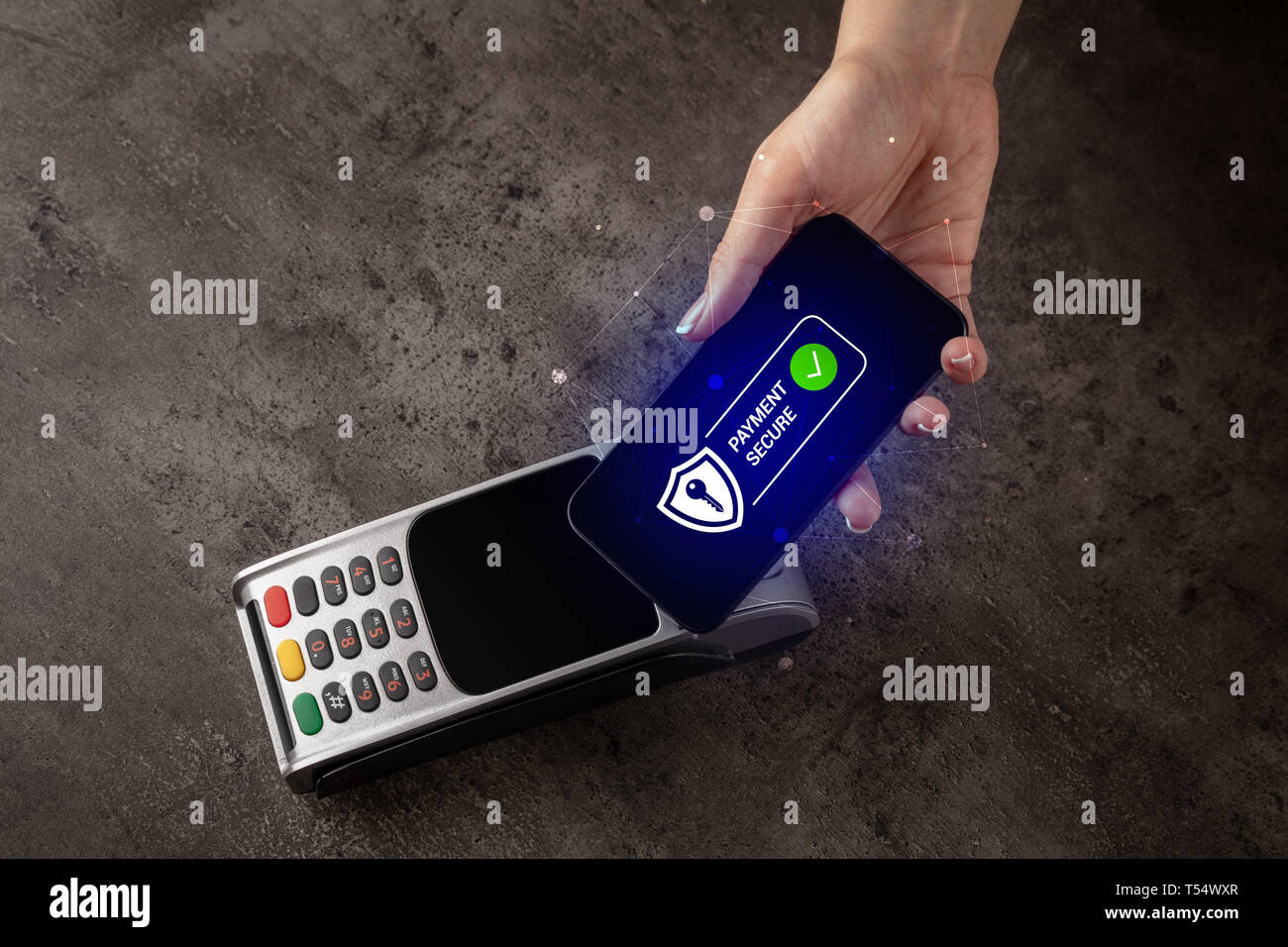 Hand paying on terminal with smartphone in secure payment system  - Stock Image