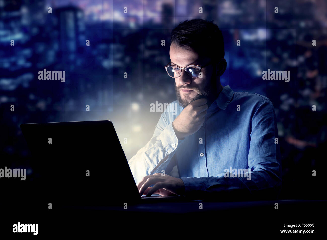 Young handsome businessman working late at night in the office with blue lights in the background - Stock Image