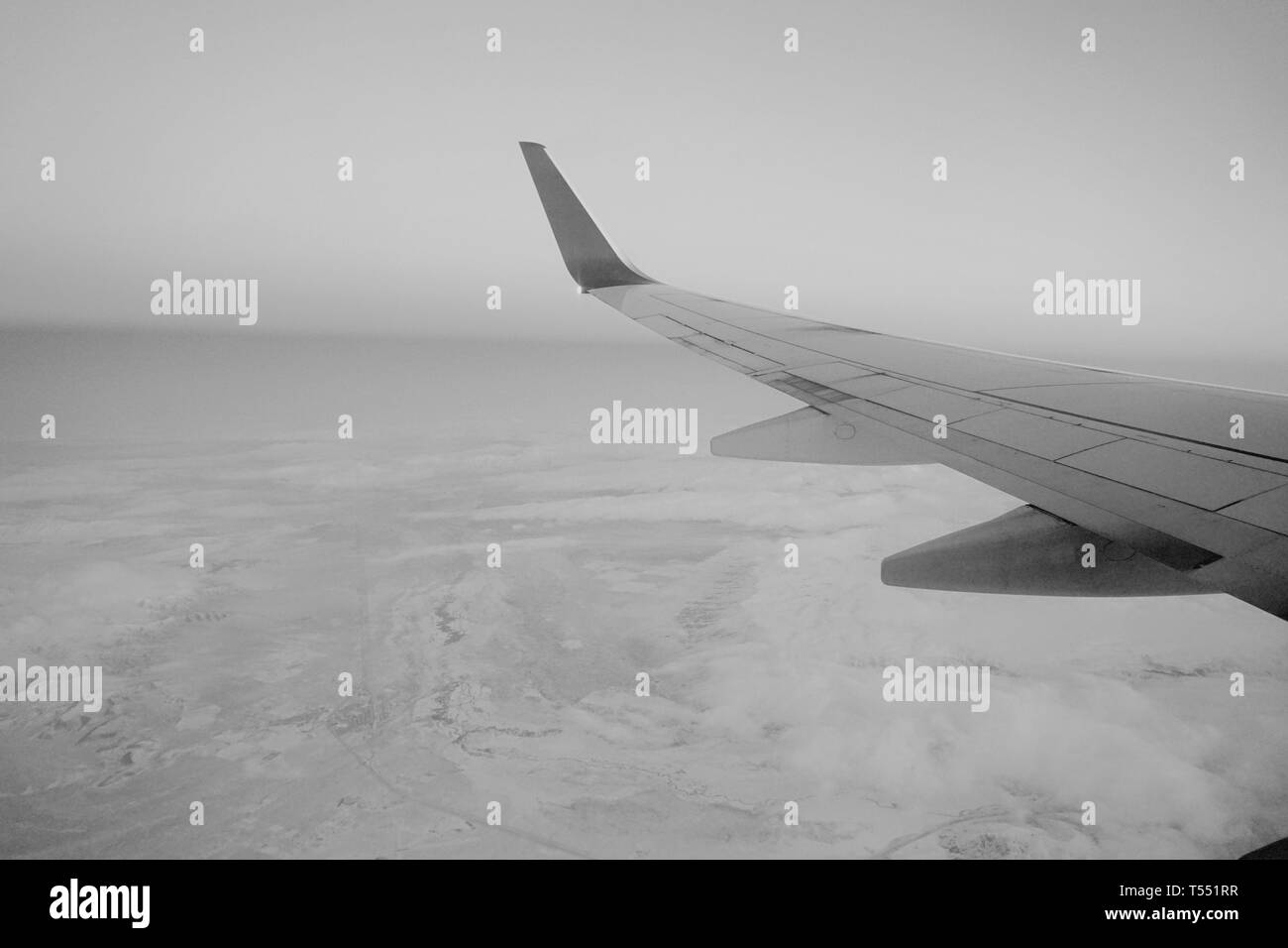 Airplane wing over snowy earth at daybreak. - Stock Image