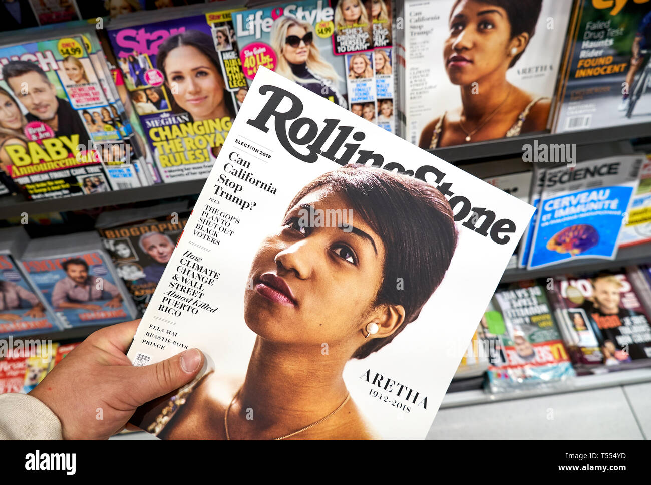 MONTREAL, CANADA - OCTOBER 9, 2018: Rolling Stone magazine in a hand over a stack of magazines with Aretha Franklin on the front cover. Rolling Stone  - Stock Image