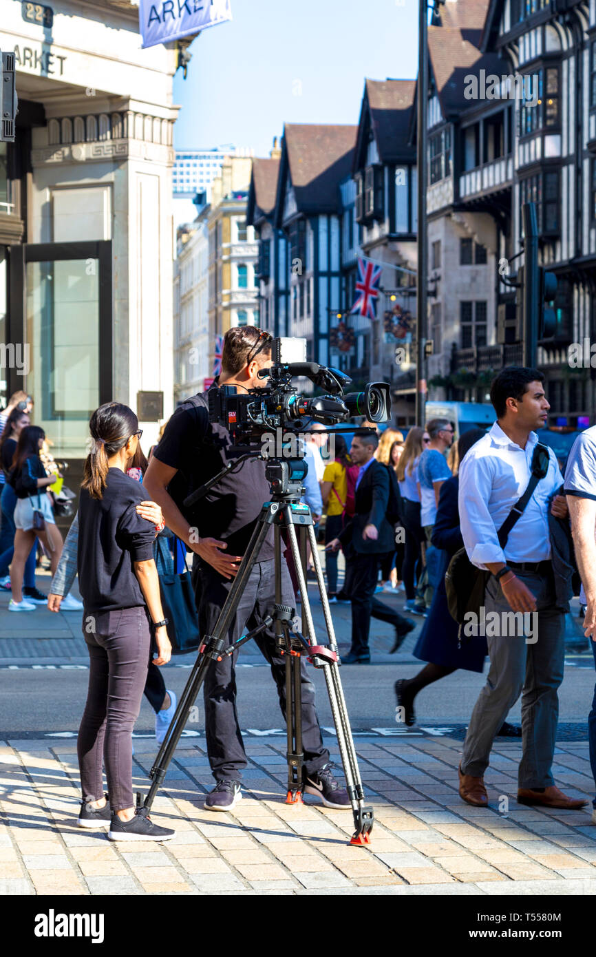 Camera man filming in the street (Regent Street, London, UK) - Stock Image