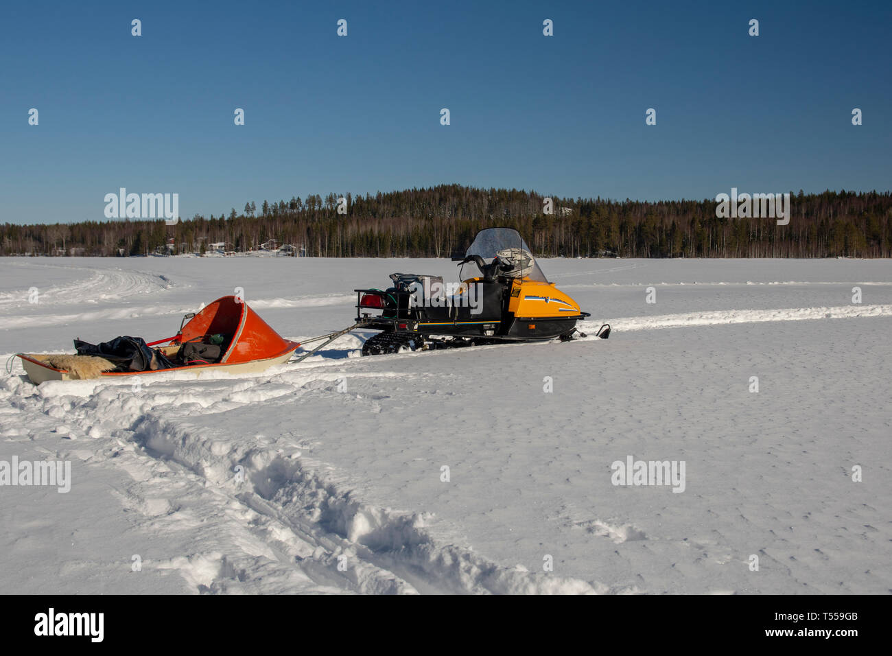 Snowmobile with a sled packed with fishing gear standing on the ice on a lake with forest and mountain in background against a blue sky, picture from  - Stock Image