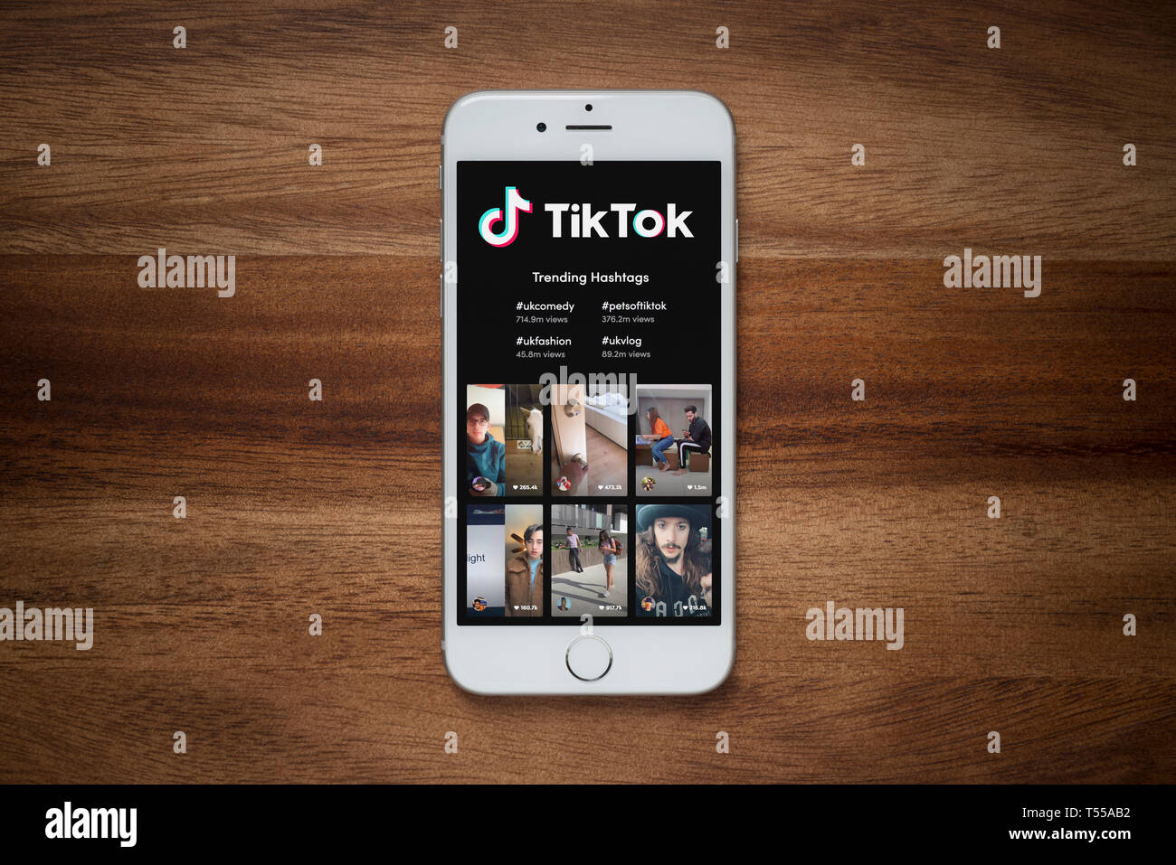 An Iphone Showing The Tik Tok Website Rests On A Plain Wooden Table Editorial Use Only Stock Photo Alamy