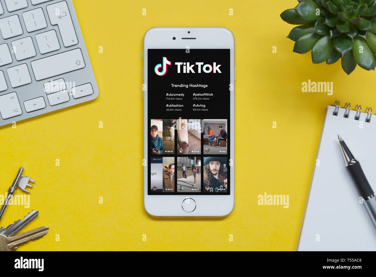 ad79495901e An iPhone showing the Tik Tok website rests on a yellow background table  with a keyboard