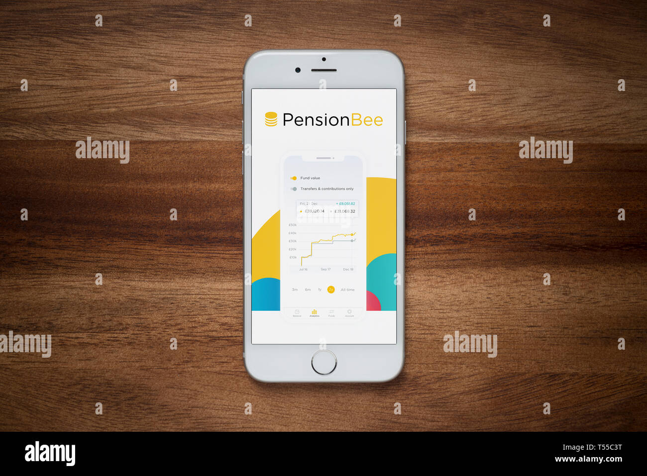 An iPhone showing the Pension Bee website rests on a plain wooden table (Editorial use only). - Stock Image
