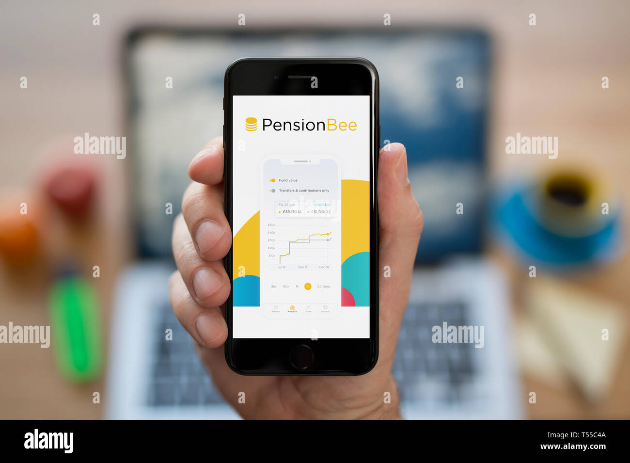 A man looks at his iPhone which displays the Pension Bee logo (Editorial use only). - Stock Image