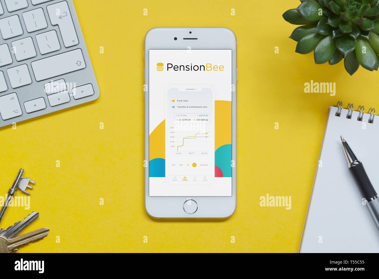 An iPhone showing the Pension Bee website rests on a yellow background table with a keyboard, keys, notepad and plant (Editorial use only). - Stock Image