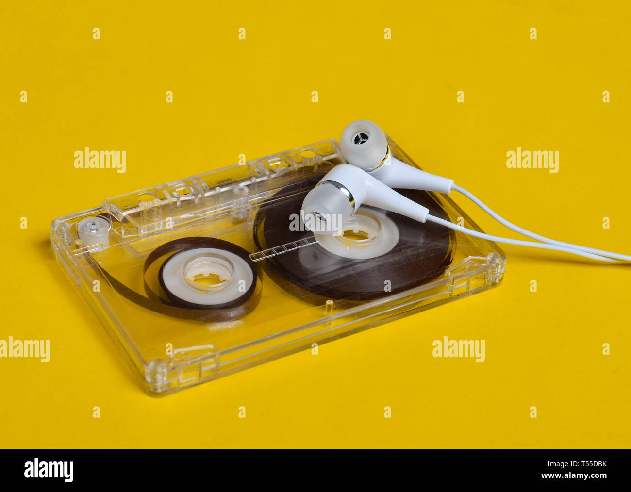 Retro technology. Plastic transparent audio cassette and white vacuum headphones on a bright yellow background. 80s. Stock Photo