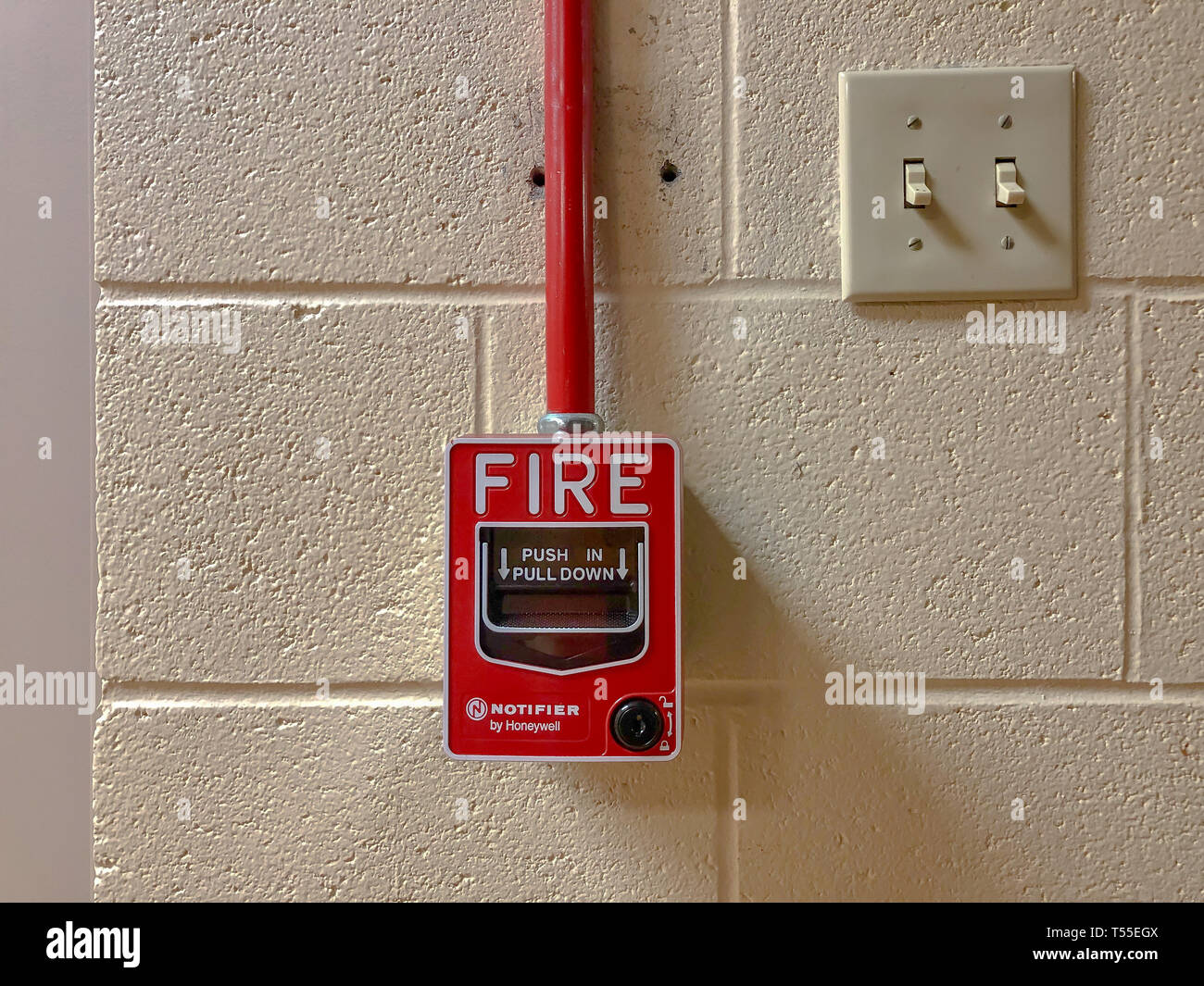 Honeywell Notifier Fire Alarm Handle Pull switch on the white wall as background for emergency case at the new factory building Stock Photo