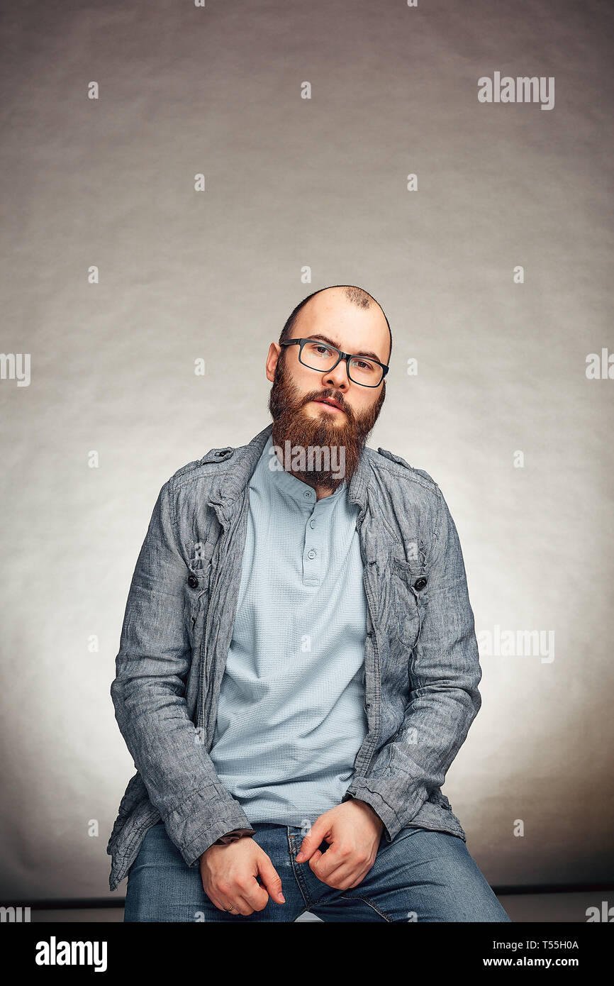 lifestyle successful young man with glasses , beard, fashionable denim jacket looking forward,male portrait in the Studio on a uniform background. Stock Photo