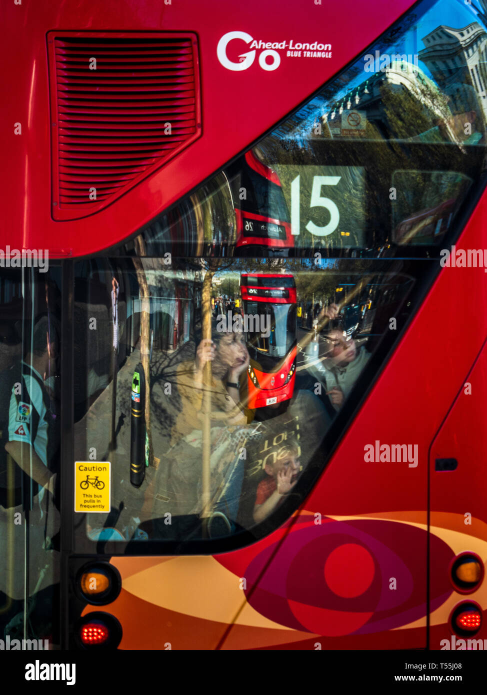 Children look out of the rear staircase window of a new London Routemaster Bus with another bus reflected in the window. - Stock Image