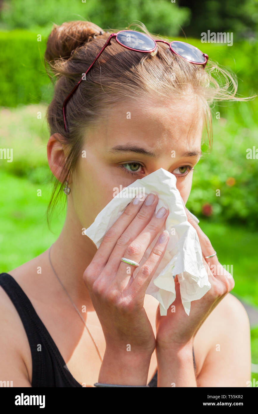 Teenage girl with hay fever and handkerchief - Stock Image