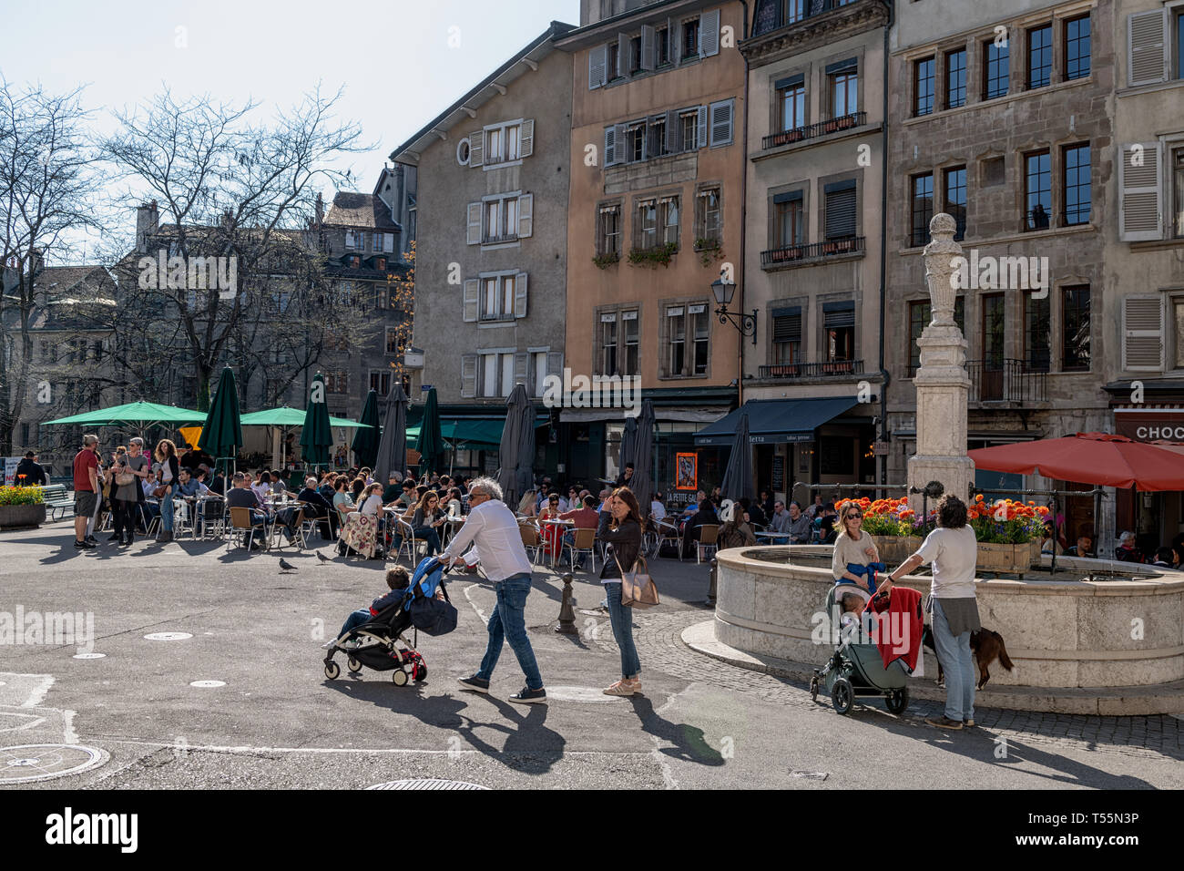 The Place du Bourg-de-Four in the old town of Geneva, Switzerland with it's fountain, restaurants and cafes and people walking about and around. - Stock Image