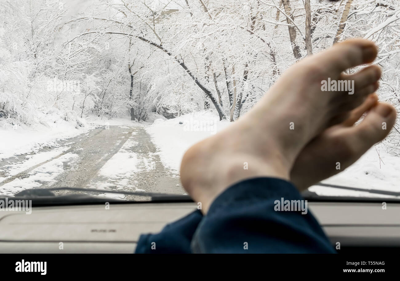 bare human feet on the windshield panel of the car on the background of snowy forest landscape and road - Stock Image