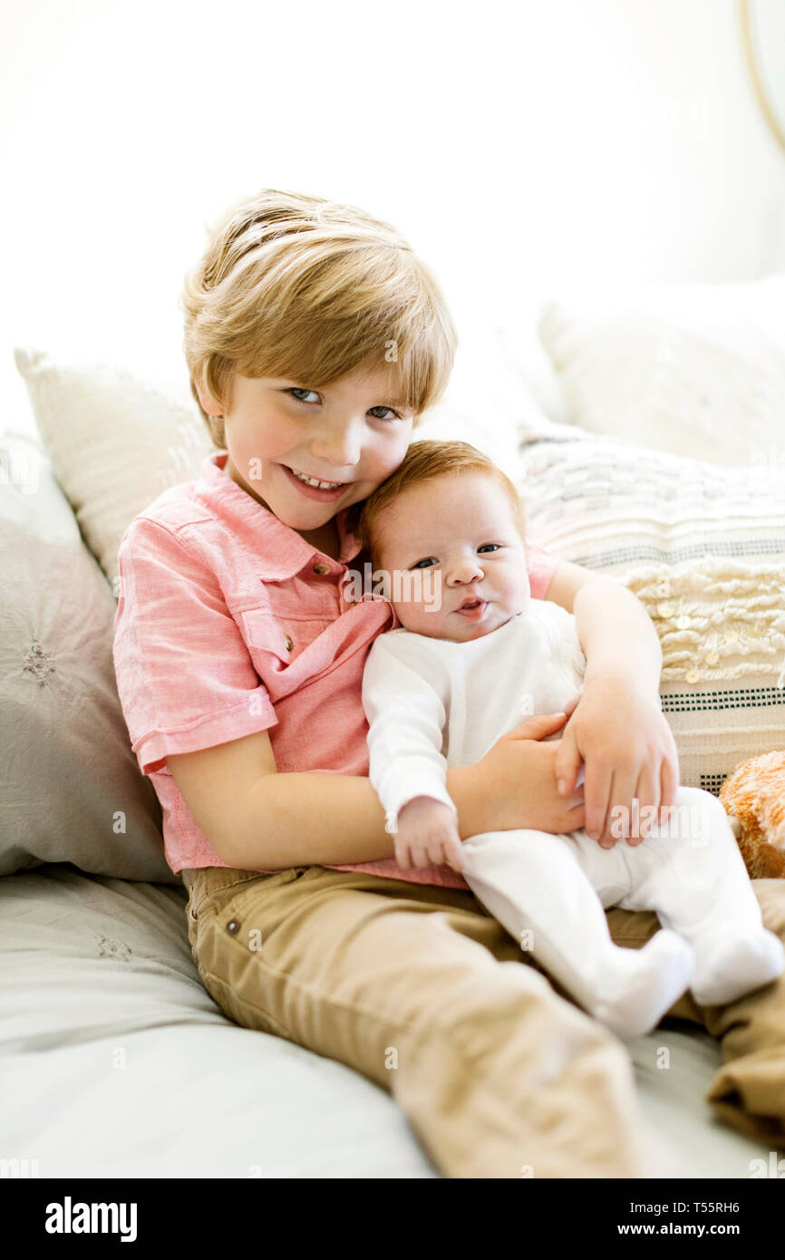 Boy holding his baby brother - Stock Image