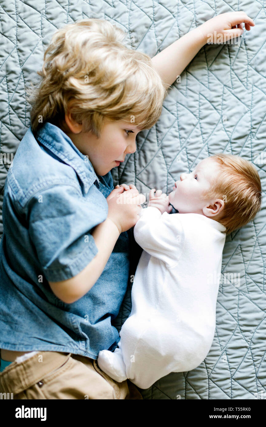 View directly above boy with his baby brother lying on bed - Stock Image