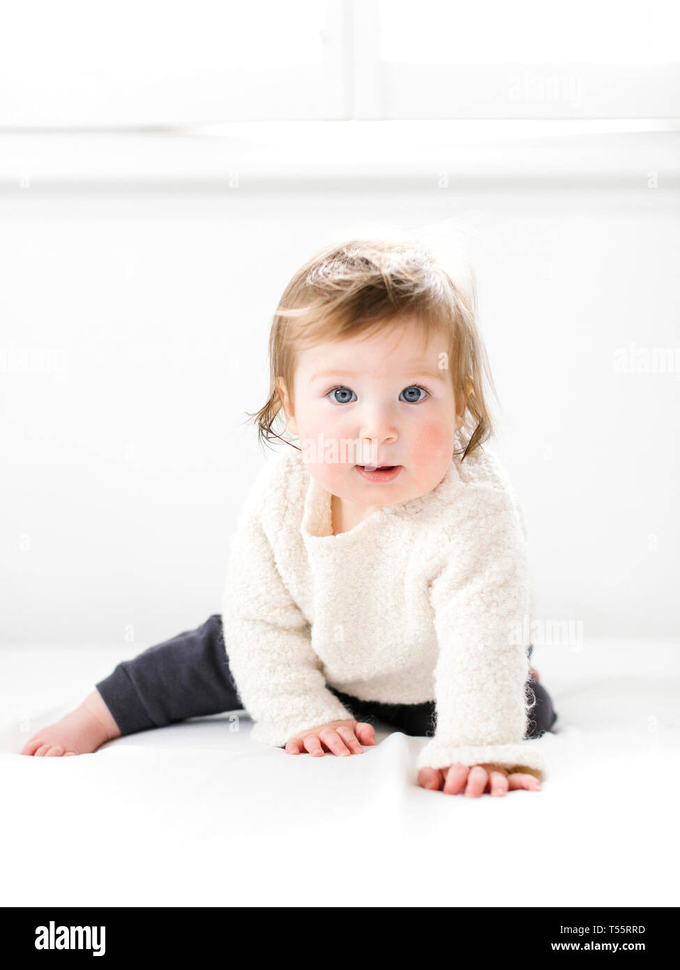 Baby girl wearing white sweater - Stock Image