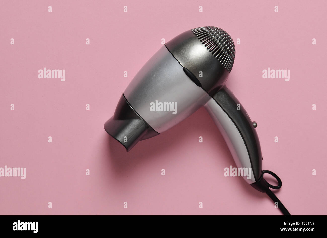 Gray plastic hair dryer on a pink pastel background. Hair care. - Stock Image