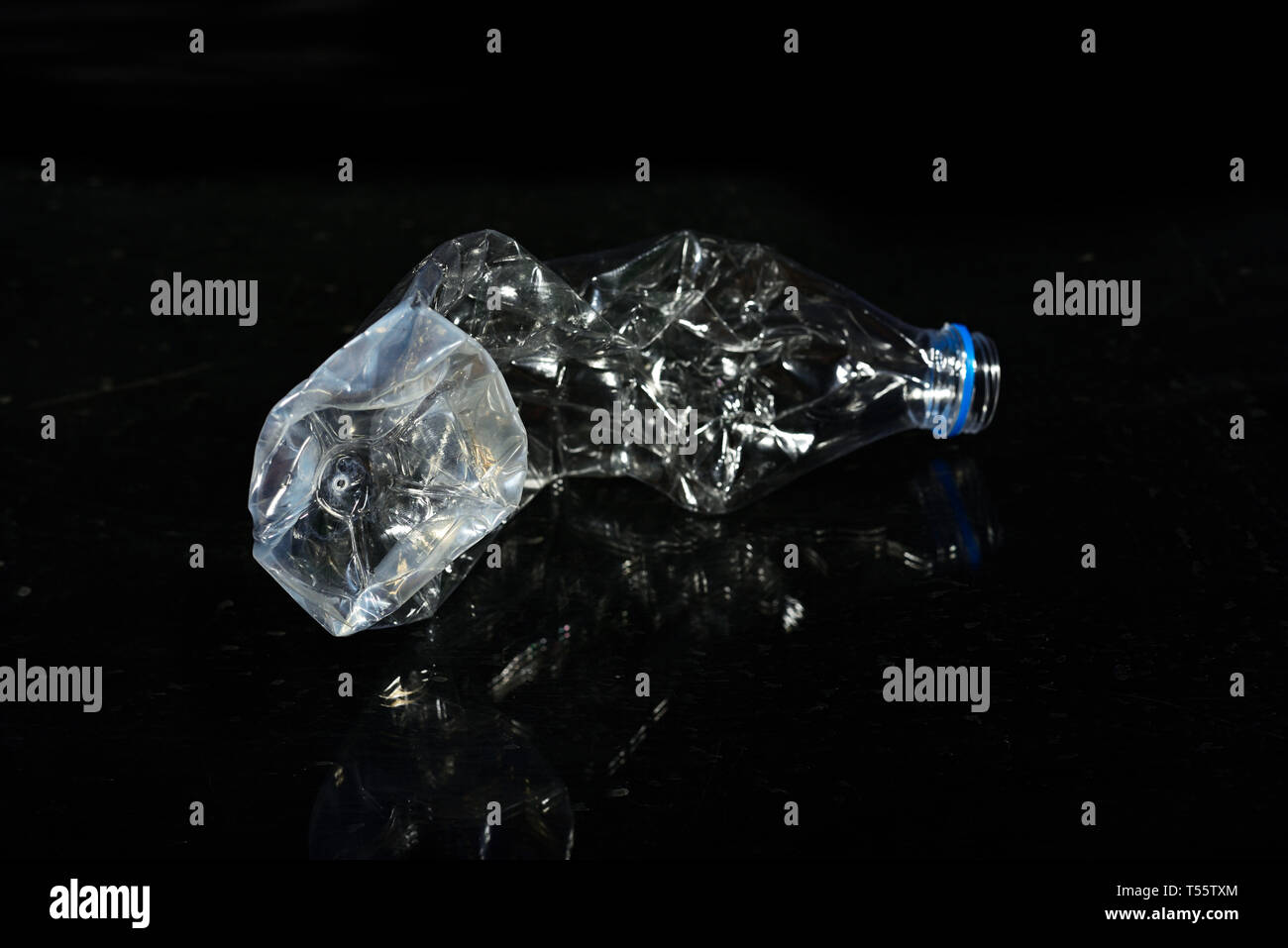Discarded plastic water bottle are isolated on black background - Stock Image
