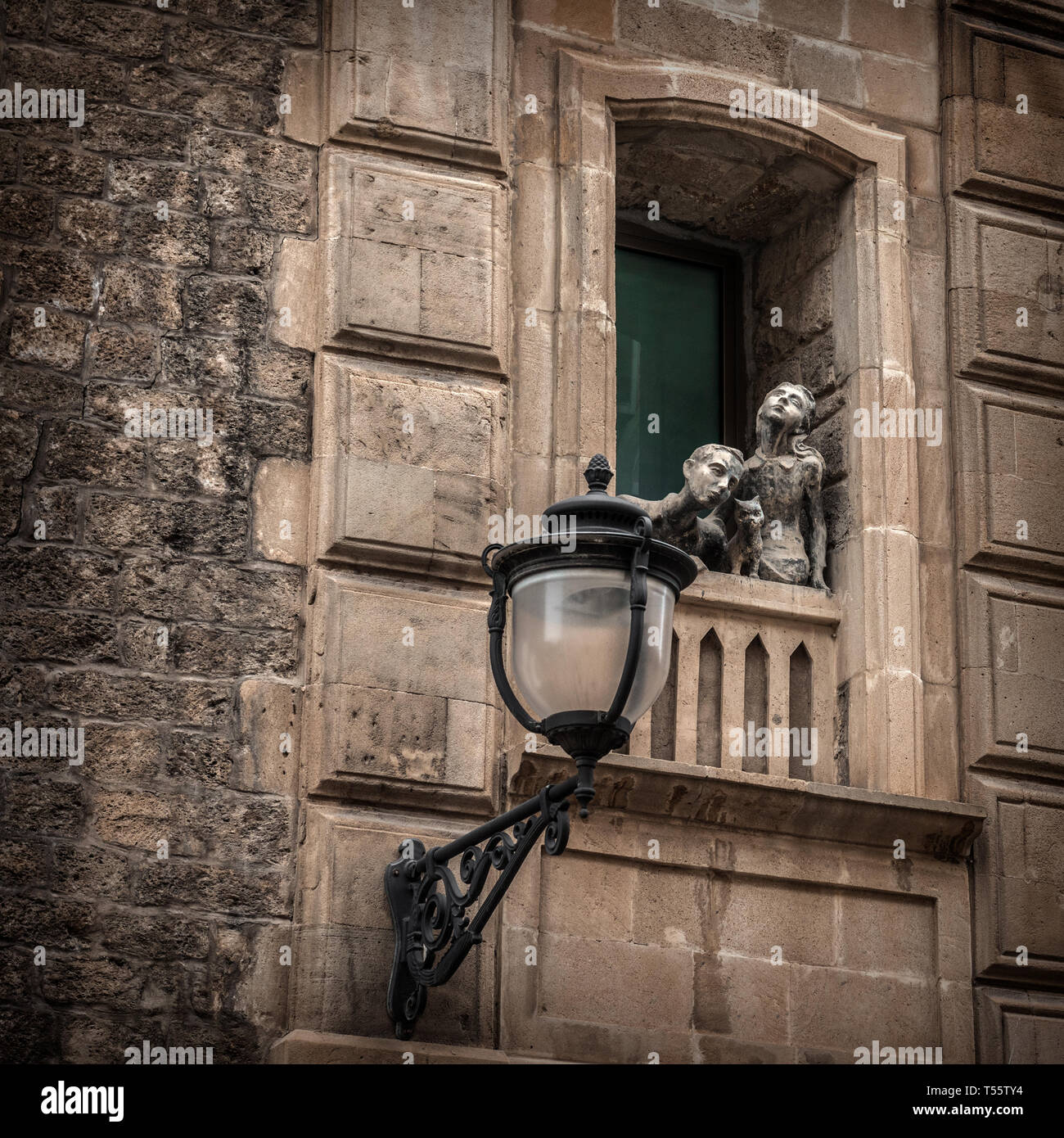 Stone figures of people in the window - Stock Image