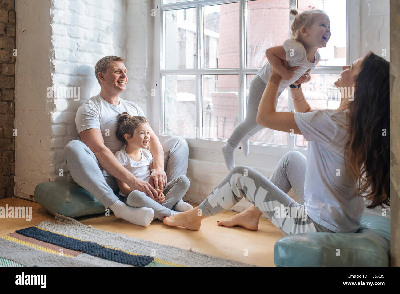 Family sitting by window Stock Photo