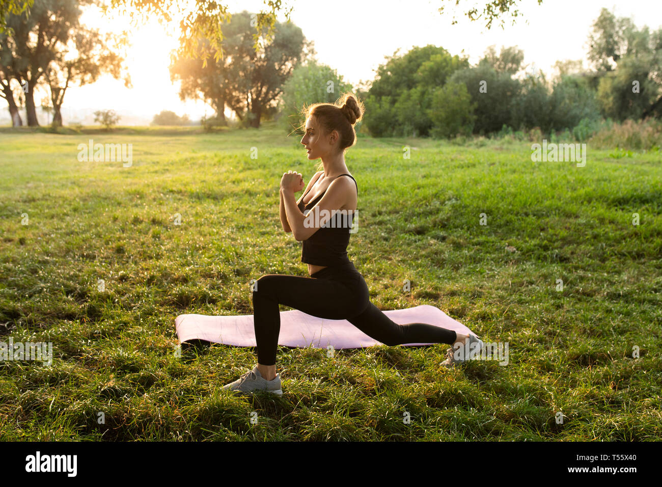 Young woman practicing yoga in park Stock Photo
