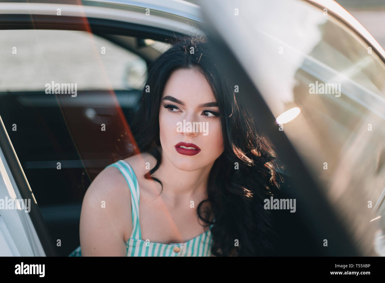 Young woman wearing red lipstick sitting in car Stock Photo