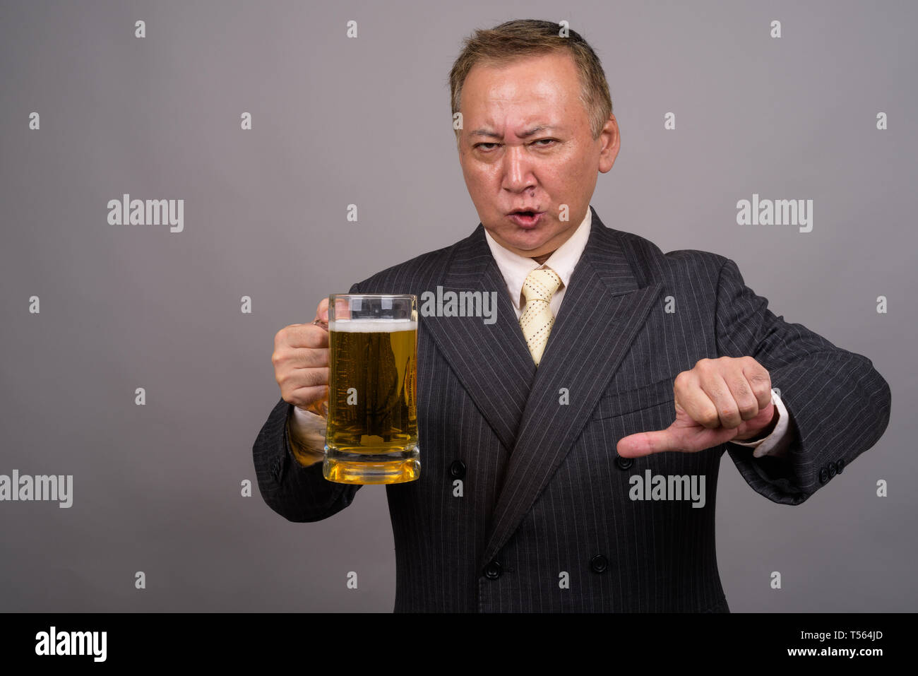Portrait of mature Asian businessman against gray background - Stock Image