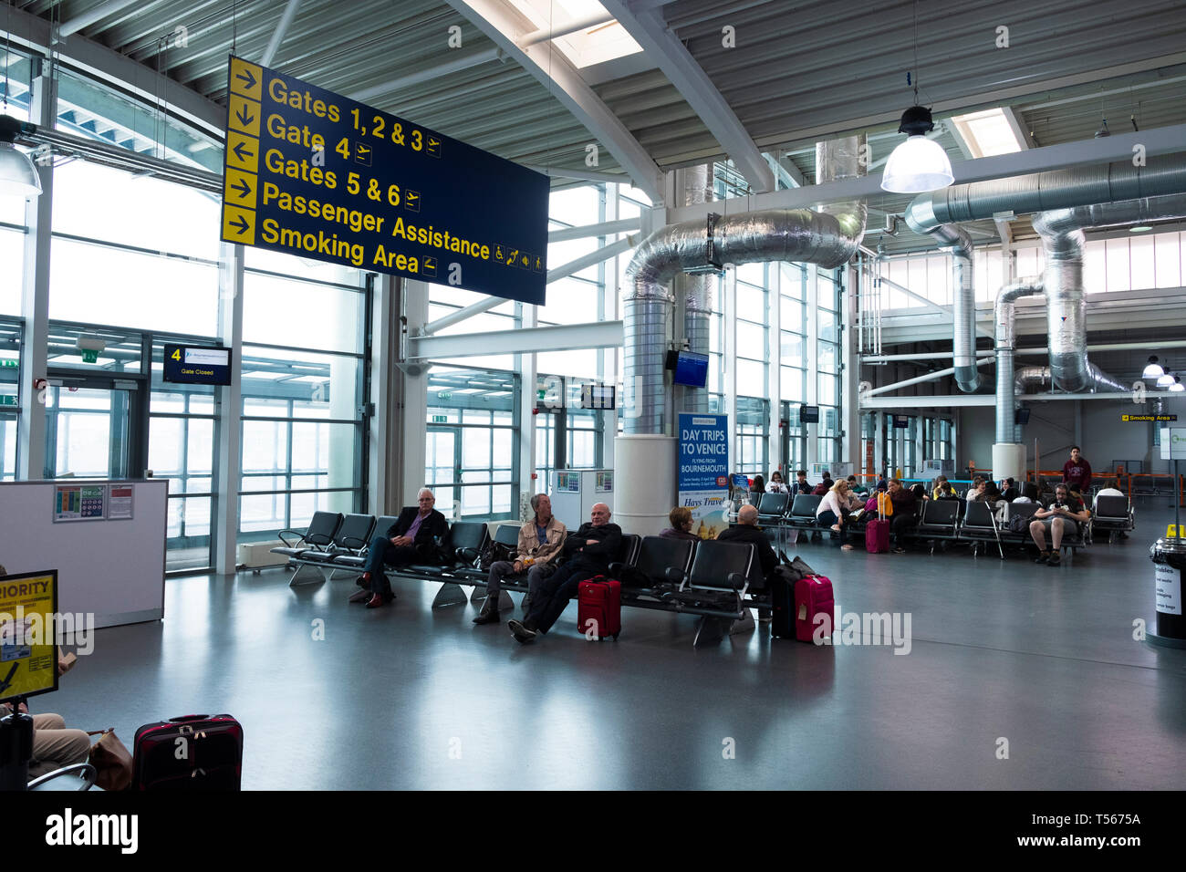 Passengers waiting in Bournemouth Airport departure hall interior with signs to gates Stock Photo