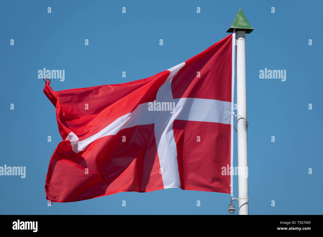 a flag of Denmark blowing before a blue sky - Stock Image