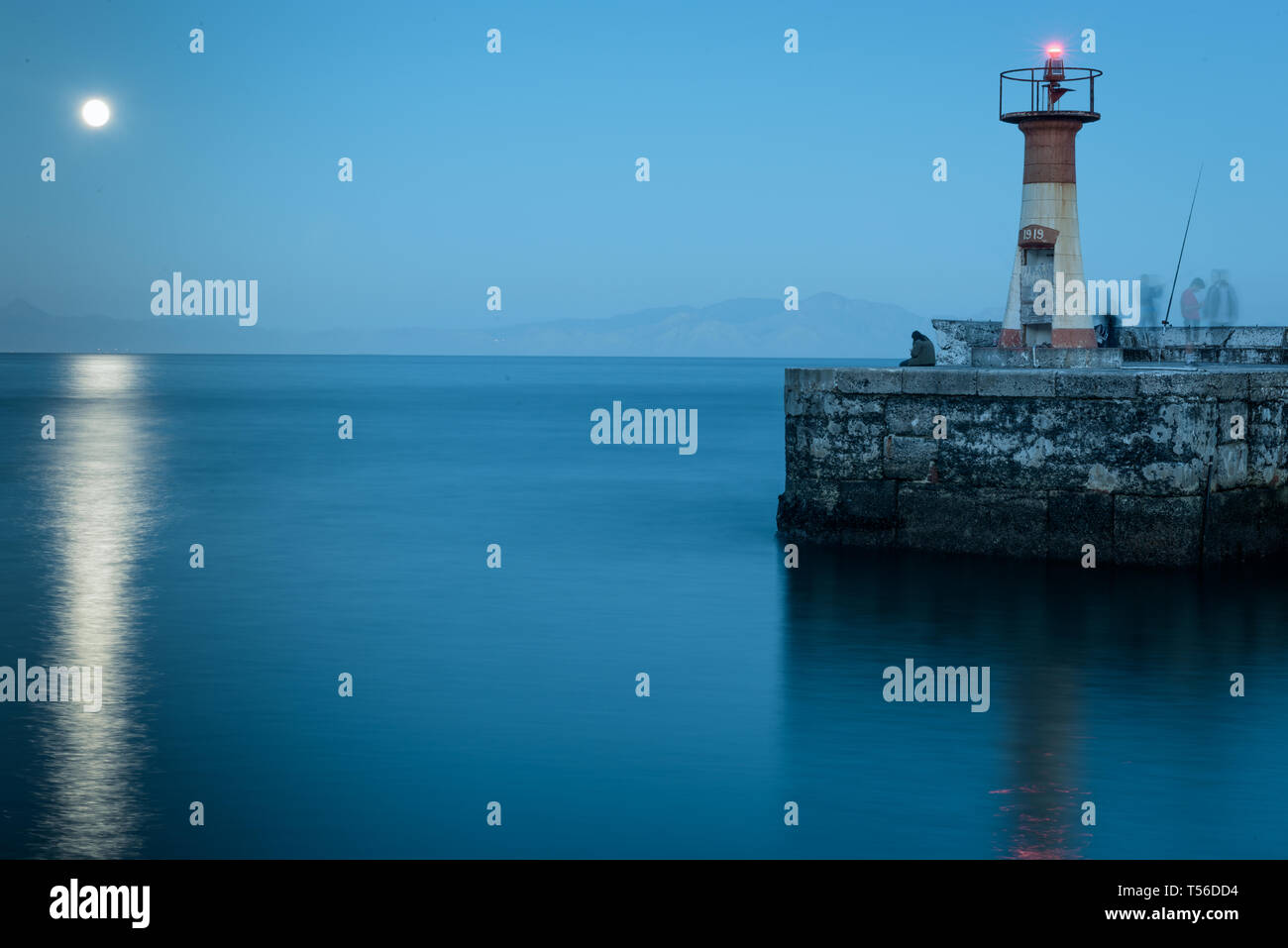 Long exposure shows activity of fishermen through ghosting, while the inactivity of a cellphone user provides a clear image in Kalk Bay, South Africa - Stock Image