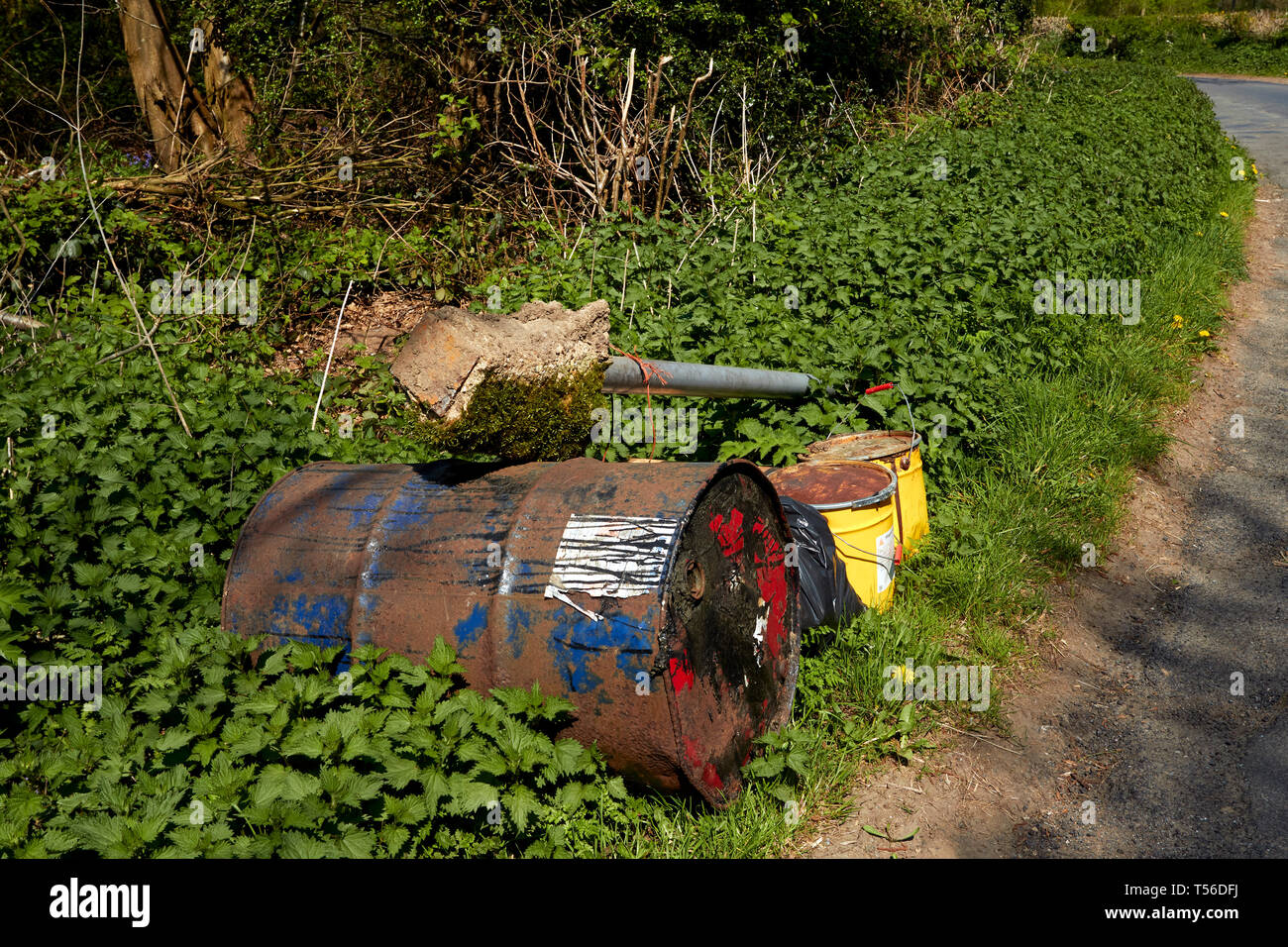 Fly-tipped rubbish along a country road in the beautiful Kent countryside - Stock Image
