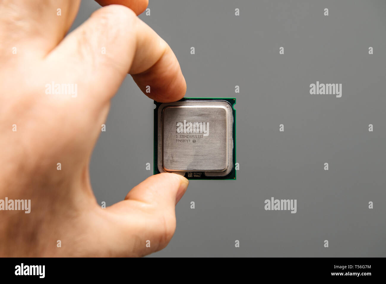 Paris, France - Apr 9, 2019: Male IT professional holding in hand new powerful CPU Central processing unit with high core count and elevated frequency Intel Xeon X5268 - Stock Image