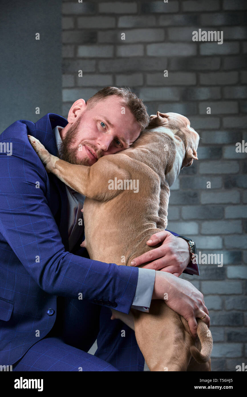 dog bulli and her owner, her loving master who holds the dog in her arms, hugs and kisses. The dog feels good on the owner's hands - Stock Image