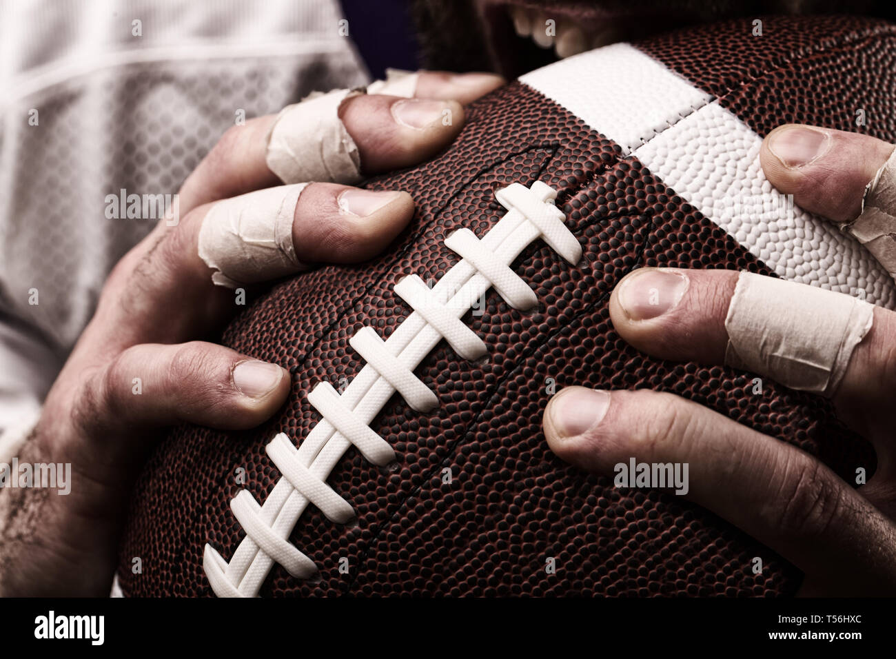 Football player with a ball in the hands, close up - Stock Image