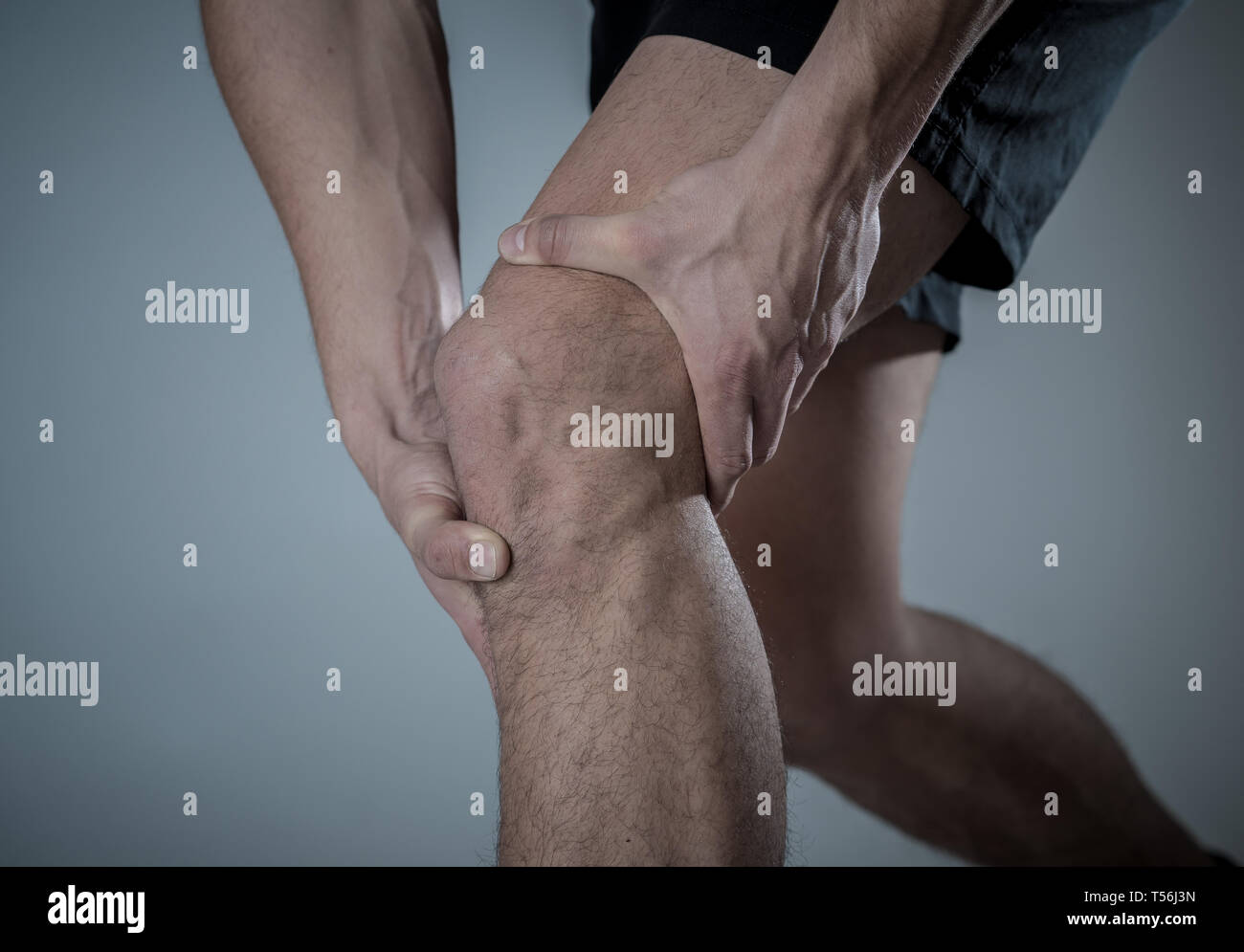 386b4f41e9 Young fit man holding knee with hands in pain after suffering muscle injury  broken bone leg