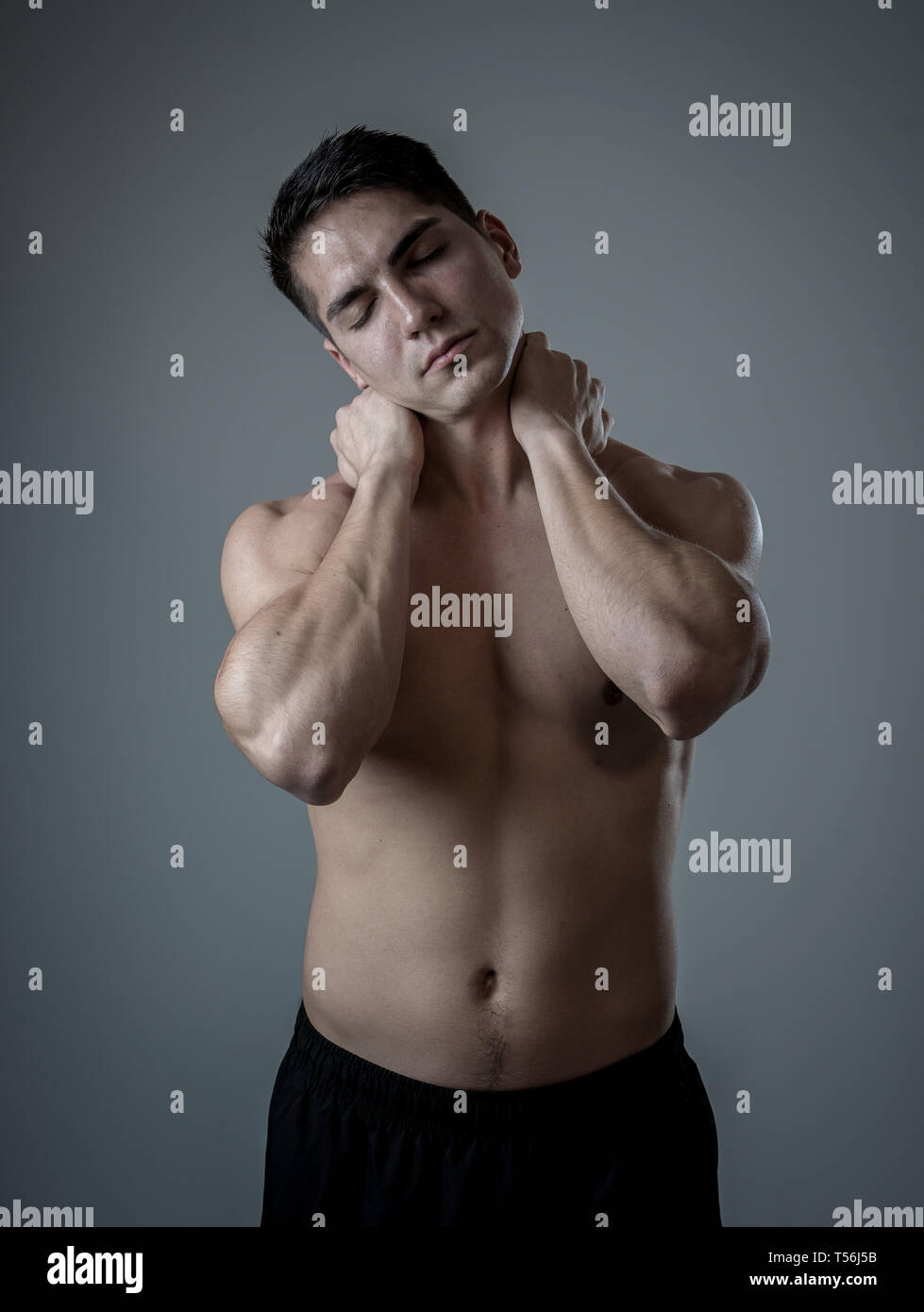 Young muscular fit man touching and grabbing neck and upper back suffering cervical pain after workout. Isolated on neutral background. In sport injur - Stock Image
